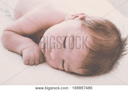 Cute Thoughtful Newborn Baby Resting On Soft Bed