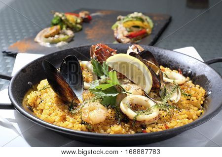 Sea food paella with sea grapes, shrimp, shellfish