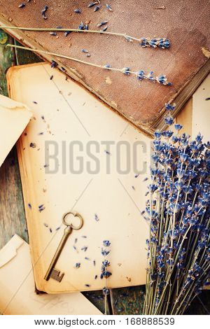 Retro still life with vintage books key and lavender flowers nostalgic composition on wooden table from above.