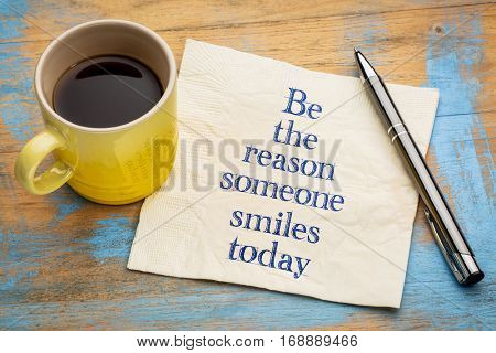 Be the reason someone smiles today - handwriting on a napkin with a cup of espresso coffee