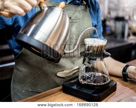 Hand drip coffee. Barista pouring water from silver teapot on coffee ground with filter. Hot coffee.