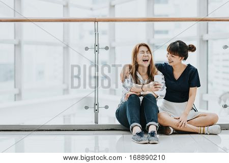 Two young happy Asian girls best friends laugh and smile while having fun with smartphone mobile indoors.