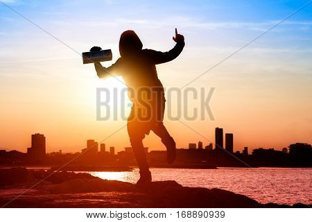 Silhouette of happy man listening music radio tape player on cityscape background at sunset - Hooded guy figure dancing on the beach with joyful winner attitude backlight image and sun halo filter