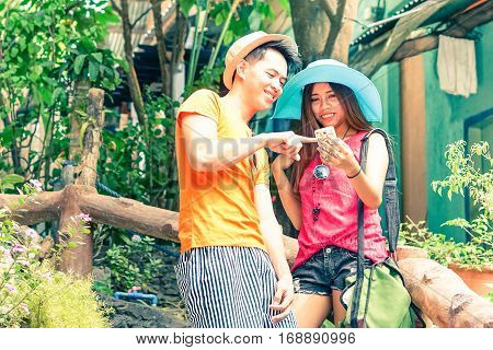 Happy filipino couple of tourists using mobile with man pointing at device screen - Young asian teenagers holding smart phone standing outdoors at summer day - Tourism and modern technology concept
