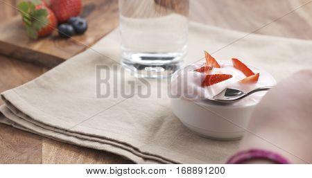 POV teen girl eating yogurt with strawberry, 4k photo