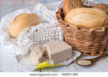 Yeast, fresh and dry granular, a wicker basket with fresh bread and a openwork white napkin on a light wooden table.