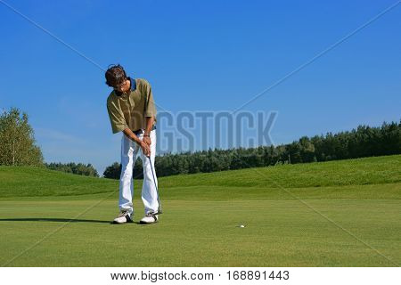 Golf Golfer thrusting the ball into the hole