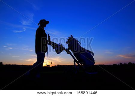 Golf woman golfer with golf bag at sunset as backgrounds