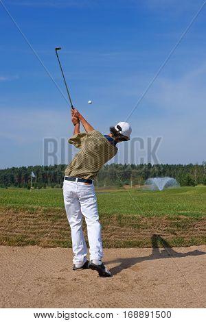 Golf golfer striking the ball from the bunker