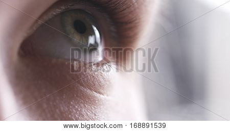 Closeup of teenage girl eye without makeup looking up, 4k photo