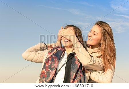 Girl make emotional surprise to her bestfriend covering eyes with hands. Happy and smiling best friends having emotional fun together around city and shopping. Memory photo about happy life moments