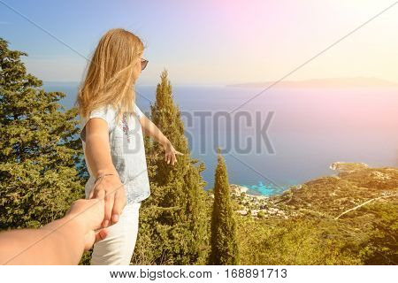 Follow me there. Beautiful young woman holds the man's hand and indicate a idyllic place to relax. Best friends couple walking hand in hand and discover new place. Carefree modern travel concept.