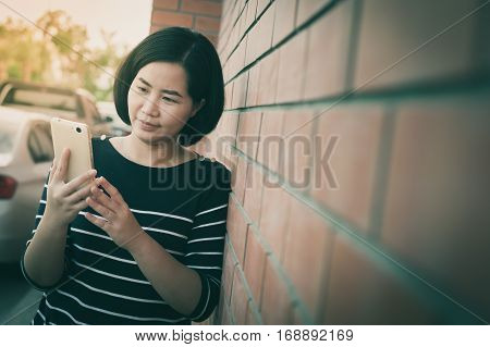 Weekend activity scene of adult Asian woman using mobile phone while standing beside brick wall with vintage filter effect. Urban lifestyle on with technology.