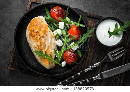 Healhty food lunch menu. Grilled chiken fillet and fresh salad from rukkola feta cheese and cherry tomatoes with white sauce.