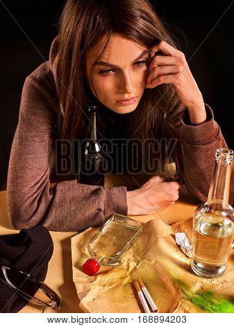 Woman alcoholism is social problem. Female drinking is cause of loneliness. She drinking alcohol in depressive mood. Mess on table because girl drunk on black background.