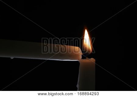 ighting tall candle with another candle in the dark, shallow focus