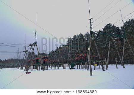The photo shows the installation of terrestrial stations electro energy. In the photo are visible pillars of odgromnikami, power lines and ceramic insulators. It is winter, Teran stations cover layer of snow.