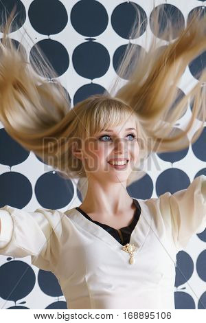 Slim blonde girl with a thick hair shakes your head and smiles for camera at the beauty salon