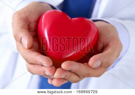Male medicine doctor hands holding and covering red toy heart closeup. Medical help cardiology care health prophylaxis prevention insurance surgery and resuscitation concept