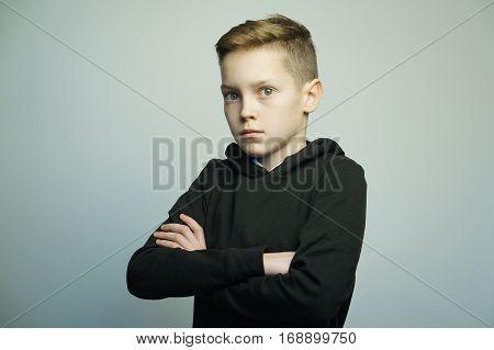 Portrait of a handsome teenage bad boy with stylish haircut, softbox lighting studio shot.
