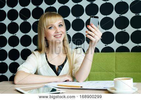Blonde girl sitting in cafe holds a mobile phone