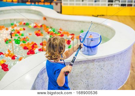 Cute Boy In The Playroom Fishing. The Development Of Fine Motor Concept. Creativity Game Concept