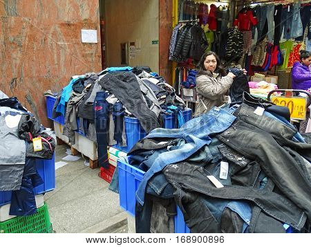 North Point, Hong Kong - February 10, 2016: A woman is standing at an big heap of jeans and other pants at a street market in North Point, Hong Kong. The selling price is displayed on large price tags.