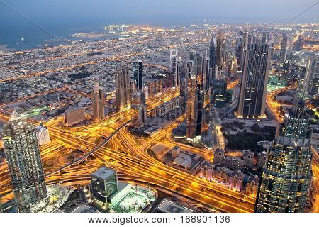 DUBAI UAE - JANUARY 28: Top view of a highway junction and the coast in Dubai UAE at sunrise. Sheikh Zayed road in Dubai downtown on January 28 2017 Dubai UAE.