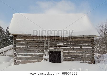 Old outbuilding sawn log cabin with it snowing and clouds and blue sky