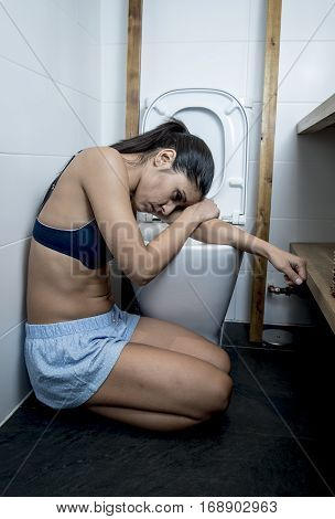 young sad and depressed bulimic woman feeling sick sitting at the floor of the toilet leaning on WC in sickness hangover alcohol abuse and nutrition disorder bulimia concept
