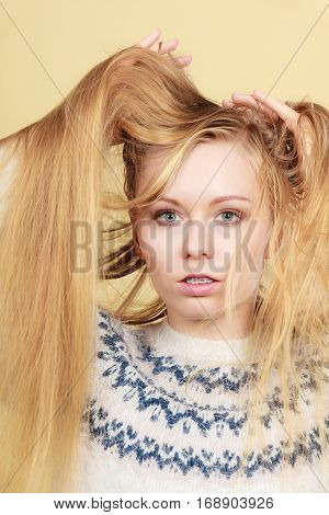 Haircare hairstyling bleaching concept. Blonde woman holding her long tangled hair closeup.