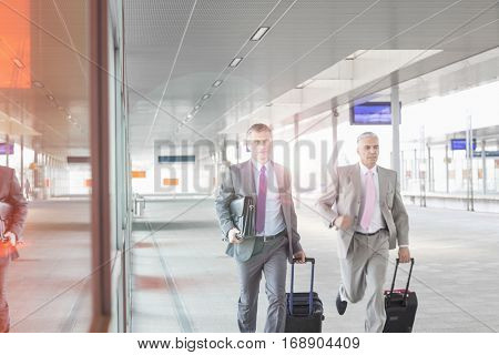Full length of businesspeople with luggage walking on railroad platform