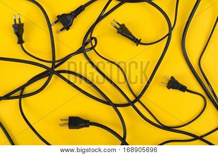 Messy of electrical cords and wires unconnected on colorful top view background messy electric equipment flat lay concept.