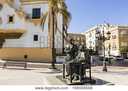 CADIZ, SPAIN - SEPTEMBER 27: The life-size, bronze statue outside an indoor exhibition centre previously the tobacco factory, shows two ladies making cigars on Spetember 27, 2016.