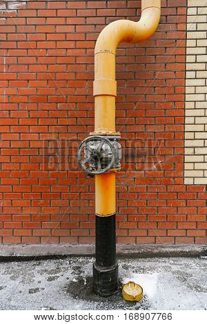 Natural gas system valve and pipe painted in yellow color in front of orange brick wall vintage color-look
