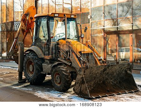 Bulldozer in the street in front of glass wall of modern building vintage color-look.