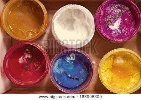 Jars with art gouache paints of different colors vintage color-look