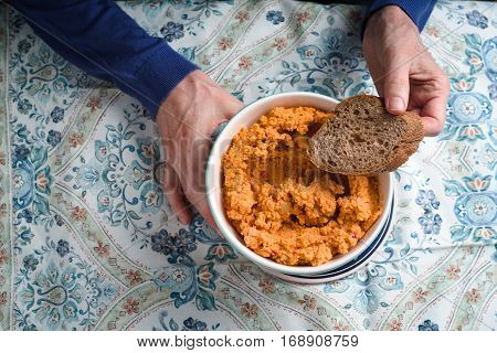 Hummus and bread in a bowl in the hand of a woman close-up horizontal