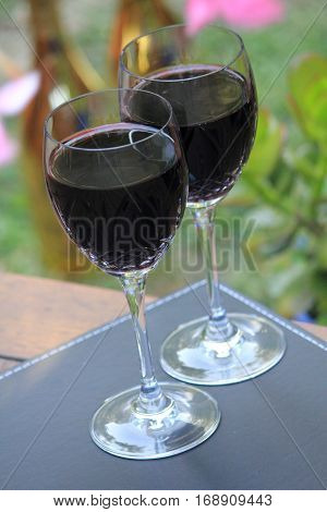 two glasses of red wine in the garden