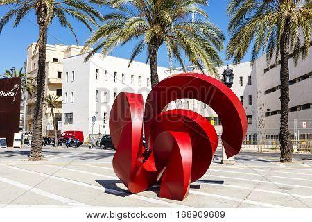 CADIZ, SPAIN - SEPTEMBER 27: Modern red metal sculpture on the street of Cadiz at the historic seafront on Spentember 27, 2017.