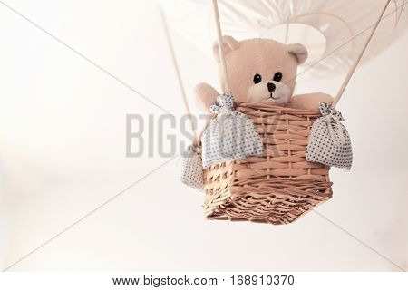Teddy bear in a aerostatic balloon toy hanging from the ceiling. Empty copy space for Editor's text.