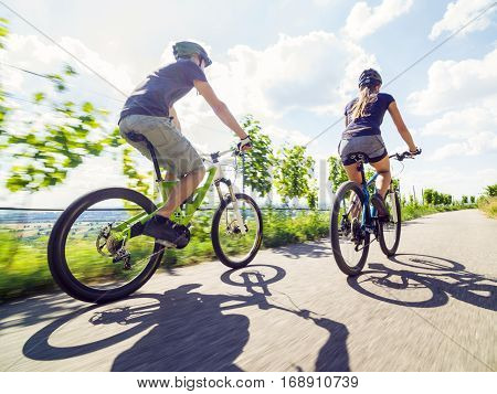 Young couple riding their mountain bikes in the summer.