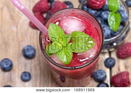Raspberry juice with the fresh raspberries and blueberries