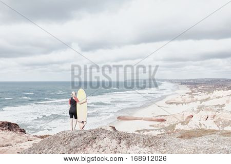 Young blonde woman wearing shorty wetsuit, standing on edge of cliff with surfboard in her hand, reading waves and preparing for surfing session - water sports concept. Baleal, Peniche, Portugal