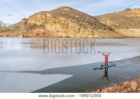 male paddler in drysuit  is enjoying stand up paddling on a partially frozen lake in Colorado - Horsetooth Reservoir near Fort Collins