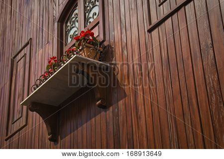 A window with balcony of a vintage wooden house. A below angle view.