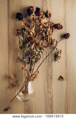 Bouquet of dried and wilted roses in the glass vase lying on wooden floor.