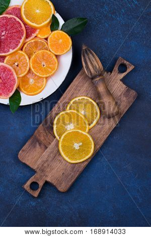 Fresh oranges, grapefruits and madarine slices on dark blue stone background. Rustic kitchen utensils: wooden cutting desk and squeezer. Top view with copy space