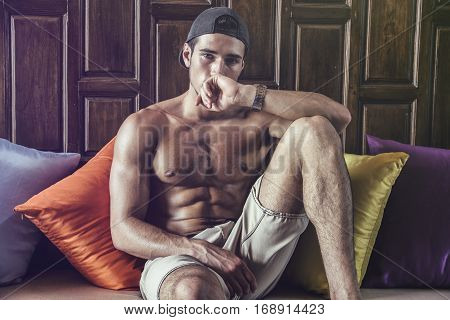 Shirtless athlete lying on pillows and looking at camera. Horizontal indoors shot.
