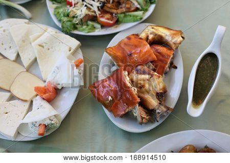 Dish with roasted young pig. Food table background.